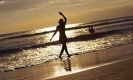 silhouette-young-woman-beach-waving-toward-sea-sunset-33960267